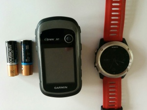 Garmin eTrex 30 next to 2 AA batteries and my Garmin Fenix 3